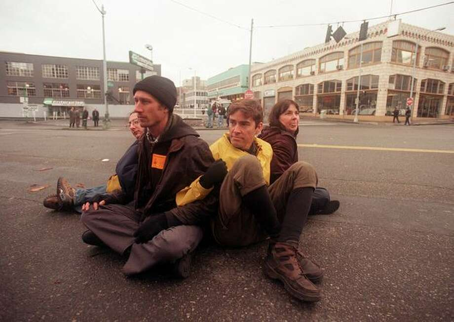Protesters from Santa Cruz, California, sit in the middle of the street at Eighth Avenue and Lenora Street while protesting the WTO on Dec. 1, 1999. Photo: Seattle Post-Intelligencer