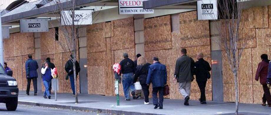 People were greeted with walls of plywood covering store windows on Sixth Avenue between Pike and Pine streets on Dec. 2, 1999. (Photo by Grant M. Haller) Photo: Seattle Post-Intelligencer