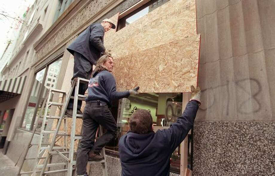 Glass workers remove plywood from storefronts on Fourth Avenue in Seattle on Dec. 3, 1999, as merchants start to let down their guard after the WTO protests smashed many storefronts and forced businesses to shut down. (Photo by Rick Giase) Photo: Seattle Post-Intelligencer