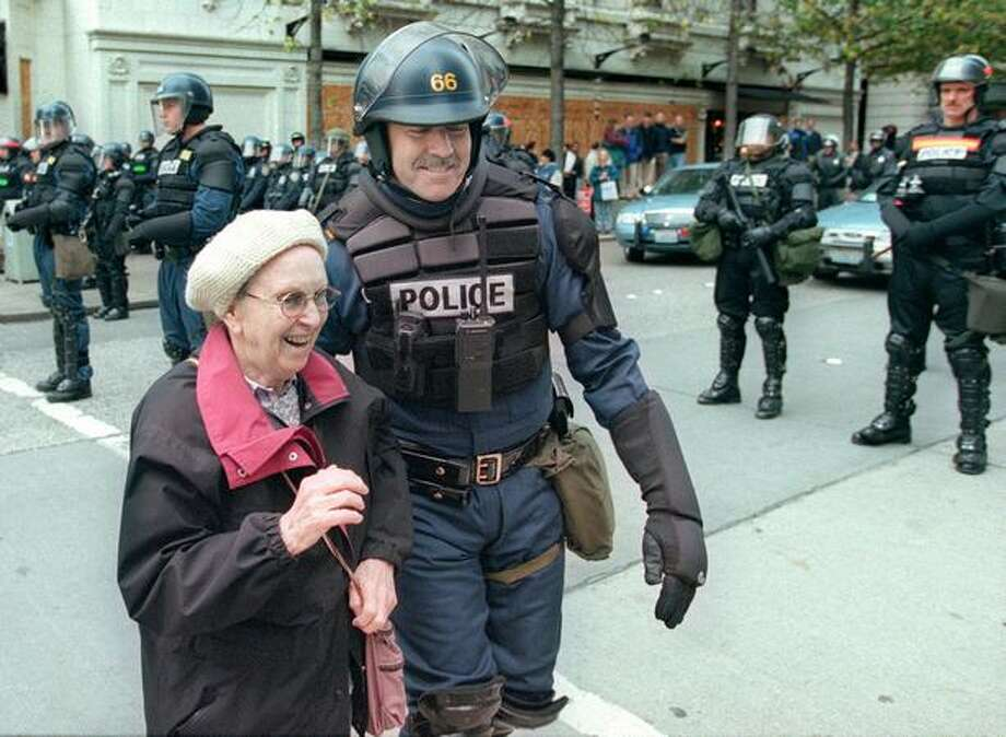Washington State Patrol Lieutenant Bruce Clark helps a woman across the street at Fifth Avenue and Pike Street on Dec. 3, 1999. Ttroopers from around the state joined Seattle Police officers and King County Sheffiff's deputies during the WTO riots. (Photo by Paul Joseph Brown) Photo: Seattle Post-Intelligencer