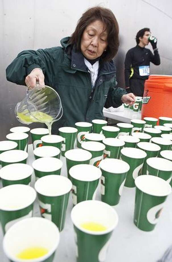 Volunteer Rosalind Howe, of Seattle, pours Gatorade prior to the start of the Seattle Marathon on Sunday. Photo: Stephen Brashear, Special To Seattlepi.com