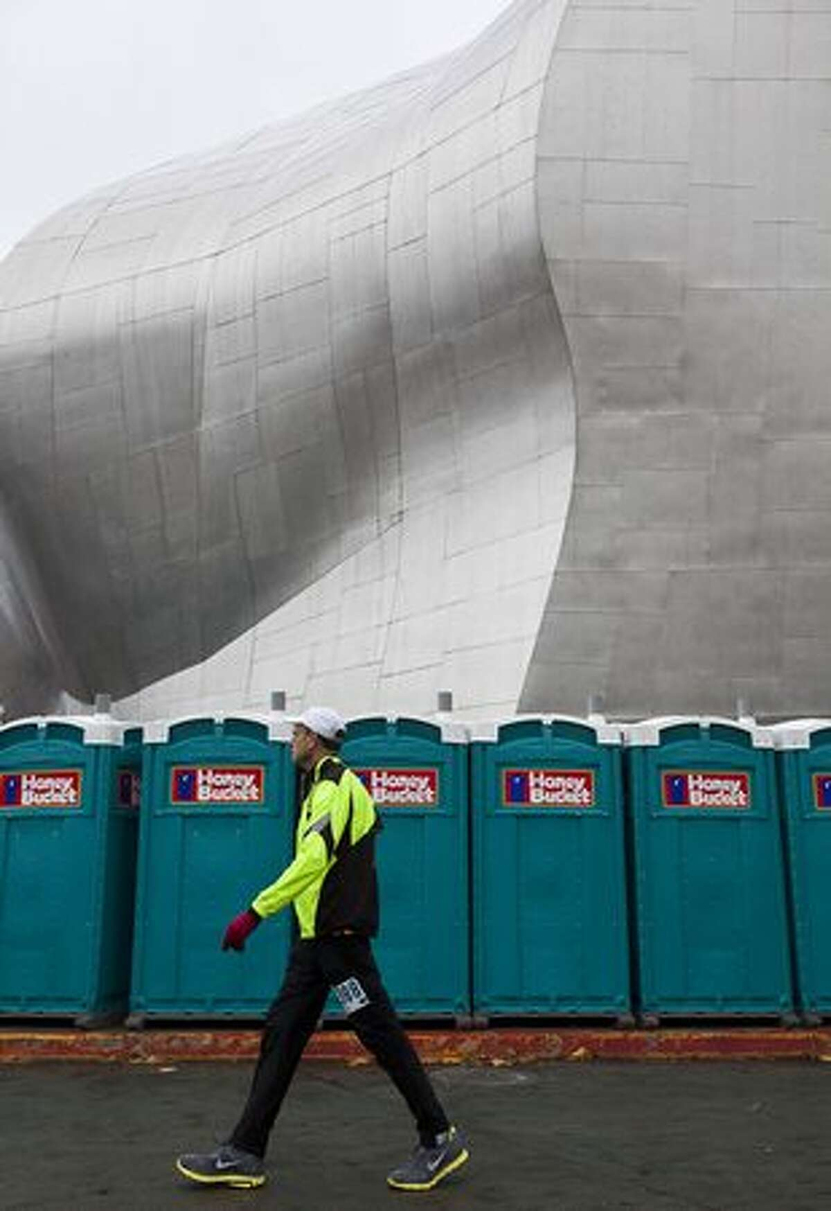 A runner passes in front a row of portable toilets in front of the Experience Music Project prior to the Seattle Marathon on Sunday.