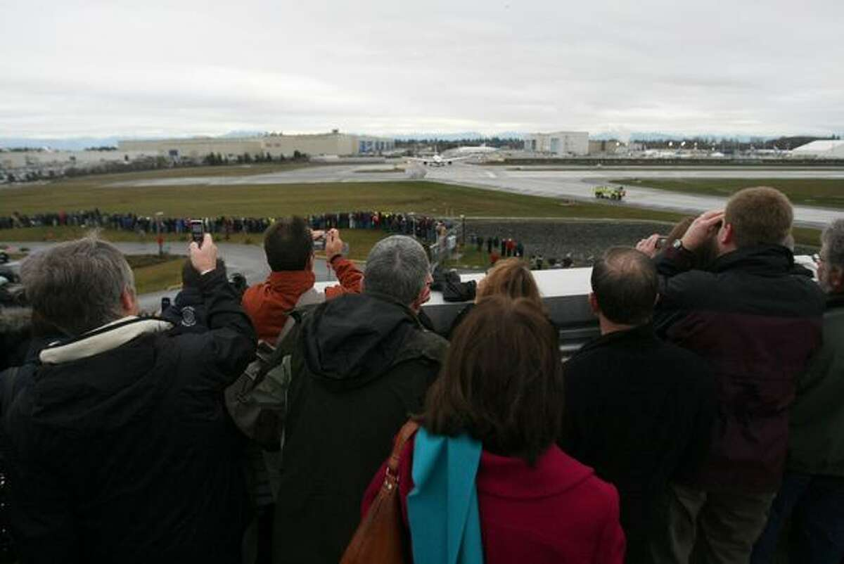 Spectators watch from the Stratodeck of the Future of Flight Aviation Center as Boeing's 787 Dreamliner rolls onto the runway to make its first flight at Paine Field in Everett.