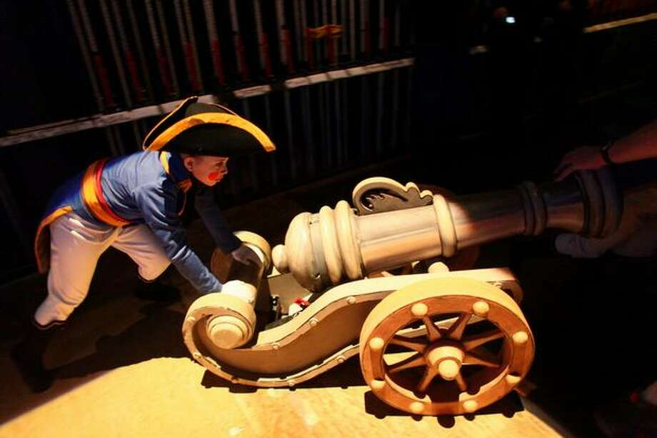 "A ""solider"" wheels a cannon onto the stage for the fight scene. Photo: Joshua Trujillo, Seattlepi.com"