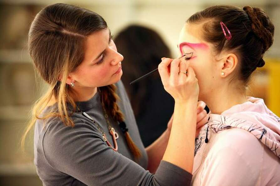 Makeup artist Ann von Moritz applies makeup to a dancer before a performance.