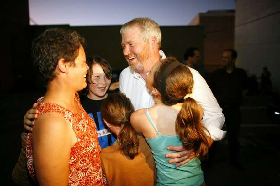 Candidate for Seattle mayor Mike McGinn embraces his family, including from left, wife Peggy Lynch,
