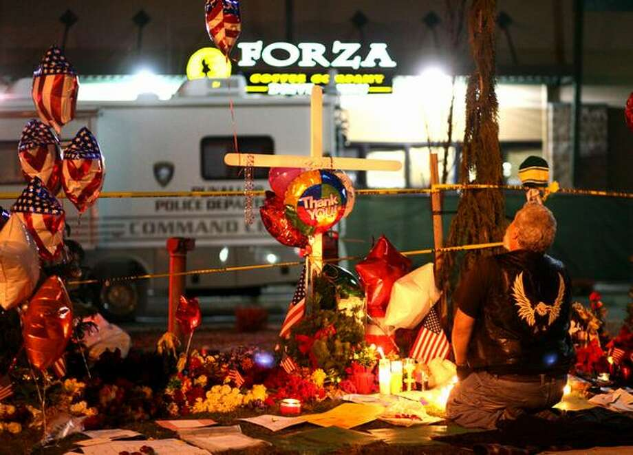 A mourner kneels at a roadside memorial in front of Forza Coffee Company in Parkland on Dec. 2, 2009, after a candlelight vigil at the nearby Lakewood Police Department. Four Lakewood police officers were shot and killed at the coffee shop in an surprise attack. The man who killed the officers was later shot and killed by a Seattle police officer after an extensive manhunt. Photo: Joshua Trujillo, Seattlepi.com