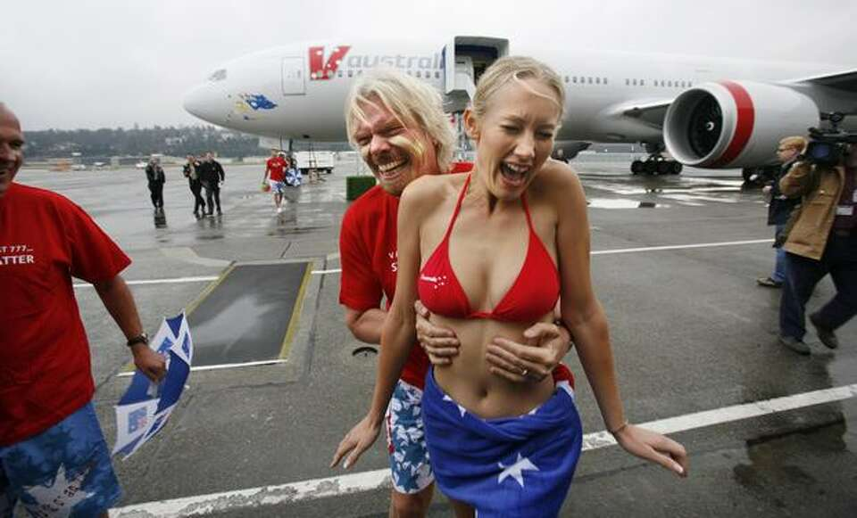 Sir Richard Branson, co-founder of V Australia, a new airline, surprises Catherine Blackbee, a fligh