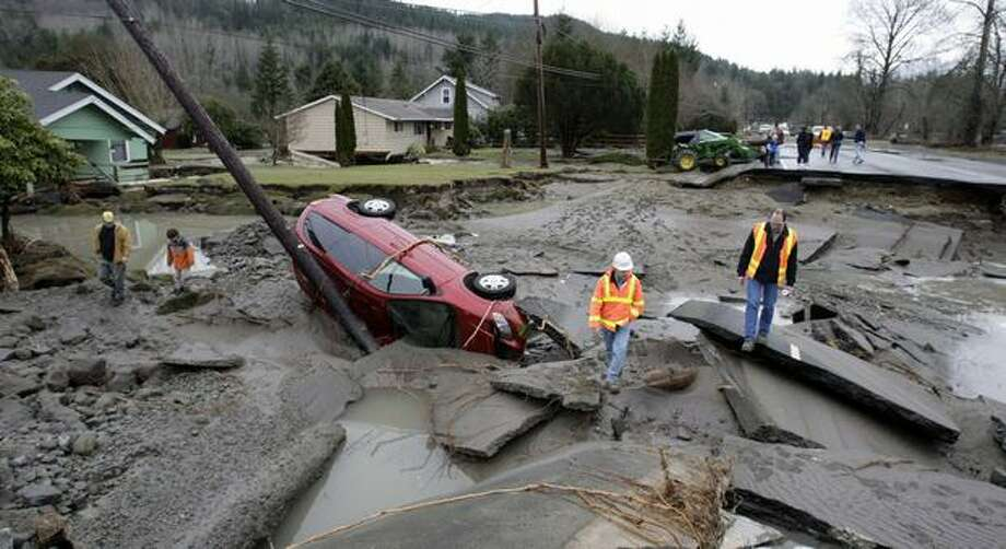 The Washington State Department of Transportation inspects Highway 202 just east of Fall City where the Snoqualmie River overflowed, causing the roadway to collapse on Jan. 9, 2009. No one was in the car when the roadway collapsed. Photo: Meryl Schenker, Seattle Post-Intelligencer