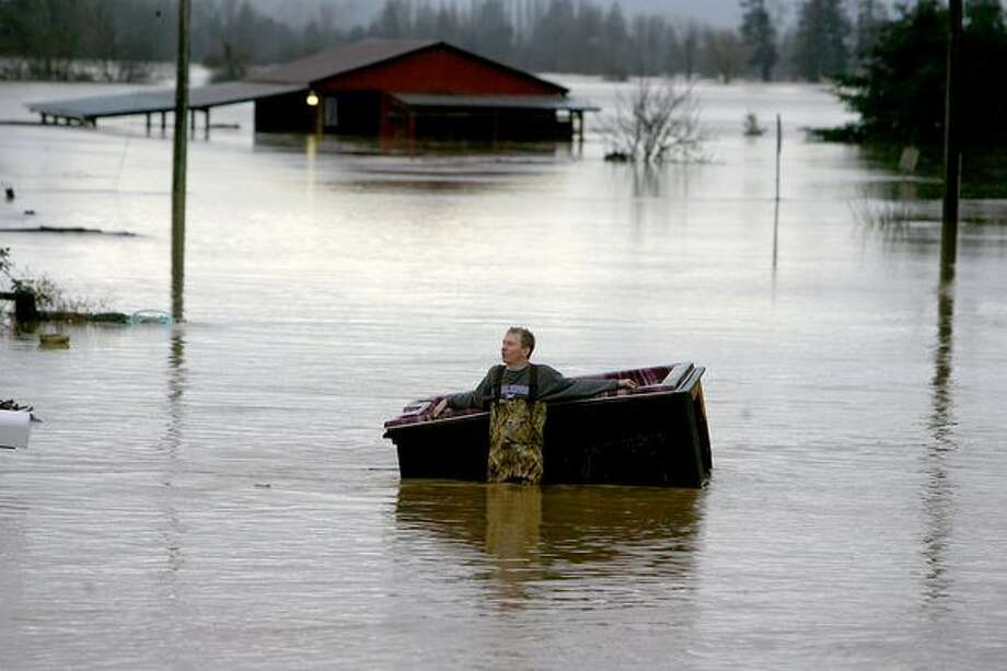Abel Puris holds onto his hot tub as he tries to figure out what to do with it after it was picked up by flood water from the Chehalis River along Military Road in Centralia on Jan. 8, 2009. Massive flooding hit the state in January, nowhere harder than Lewis County, where thousands were forced to evacuate their homes. Photo: Scott Eklund, Seattle Post-Intelligencer