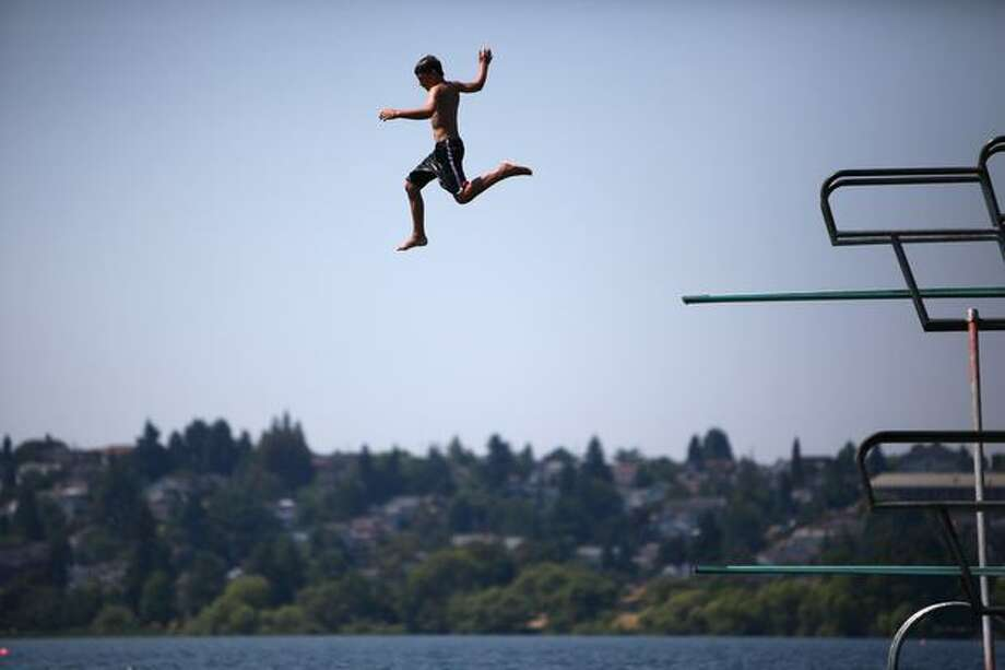A youngster leaps from a diving board at Green Lake during a record heat wave in Seattle on July 29, 2009. The mercury hit 103 degrees at Sea-Tac Airport that day, an all-time record high as Seattle enjoyed one of the warmest and driest summers in many years. Photo: Joshua Trujillo, Seattlepi.com