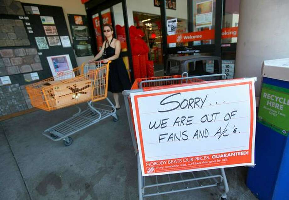 Elsie Huxtable leaves Home Depot with a ceiling fan as a sign greets customers at the store on Aurora Avenue North during a record heat wave in Seattle on July 29, 2009. Photo: Joshua Trujillo, Seattlepi.com
