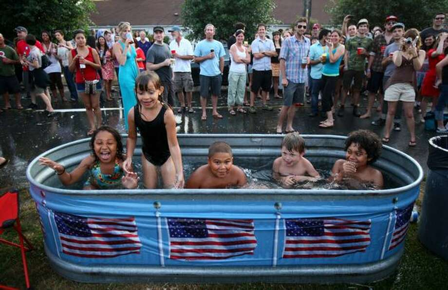 From left, Kiara Callan, 7, Tianna Kleeberger, 6, Jiyah Stewart, 8, Mikey Arieff, 5, and Michael Callan, 10, keep cool during a July Fourth street party on Minor Avenue East in Seattle's Eastlake neighborhood on July 4, 2009. Photo: Joshua Trujillo, Seattlepi.com