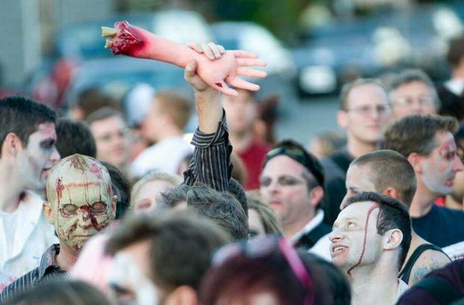 "A zombie holds up a limb before the start of a mass street dance to Michael Jackson's ""Thriller"" on July 7, 2009. Photo: Daniel Berman, Seattlepi.com"
