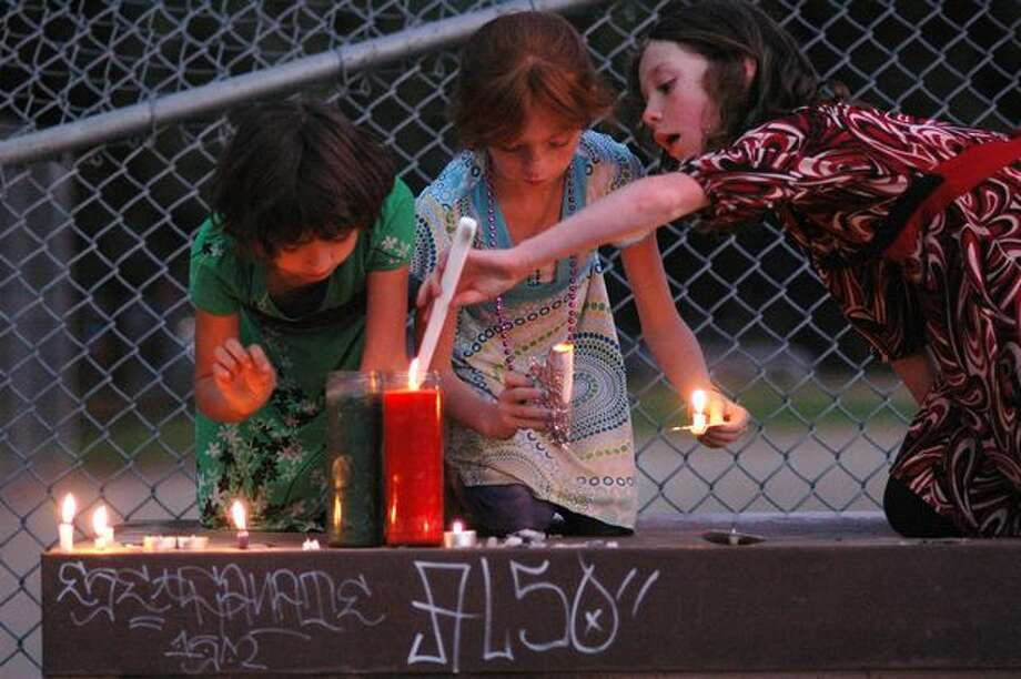 Three girls who are sisters (names withheld at request of parent) work to light candles on top of a metal container following a vigil for the victim of a stabbing at the South Park Community Center on July 23, 2009. Photo: Daniel Berman, Seattlepi.com