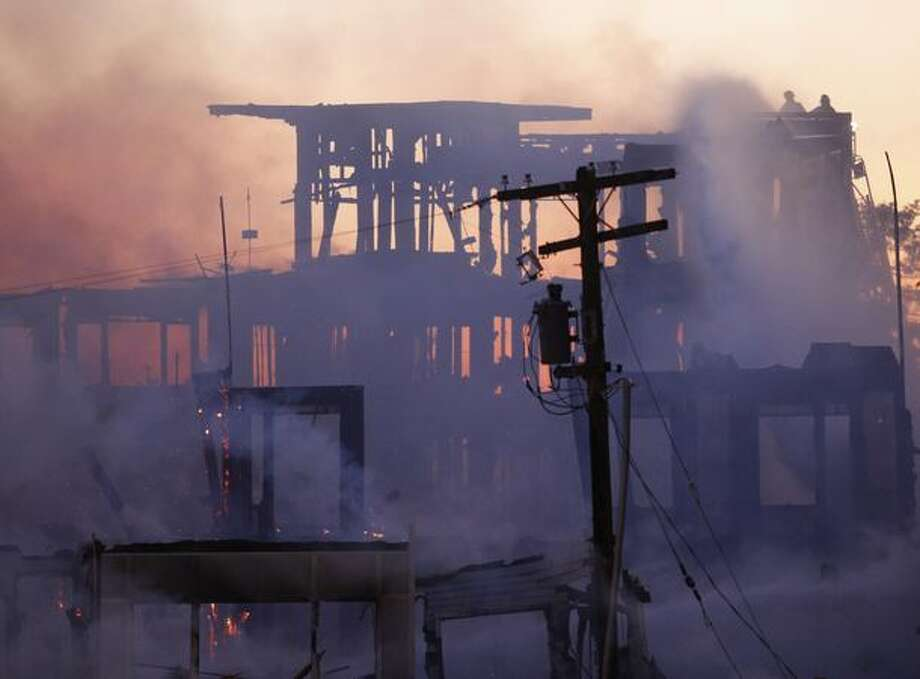A few remaining flames emerge from the fire scene during a four-alarm fire at a partially constructed Renton Highlands apartment complex on June 30, 2009. Officials estimated the loss at $11 milion. Photo: Clifford DesPeaux, Seattlepi.com