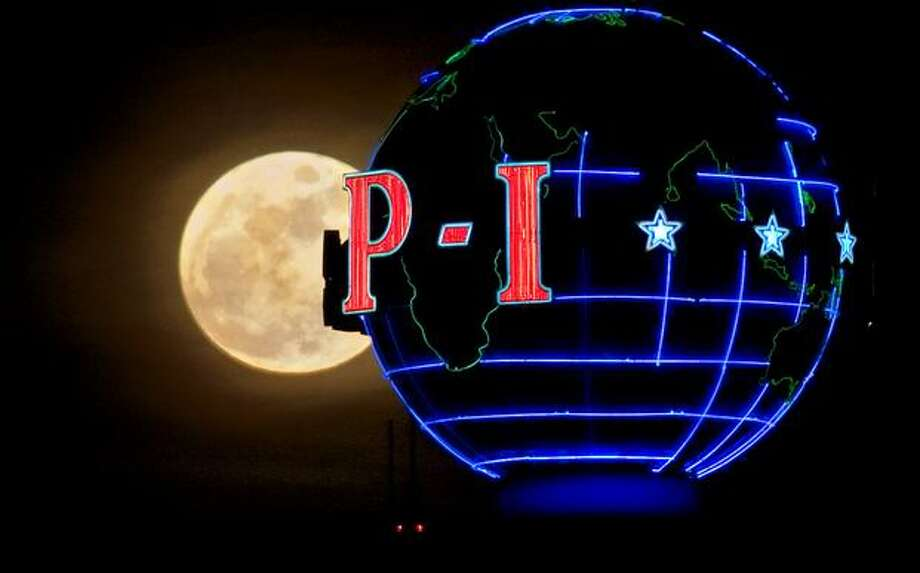A full moon rises behind the P-I globe on March 6, 2009, 11 days before the newspaper stopped the presses for good. Photo: Joshua Trujillo, Seattlepi.com