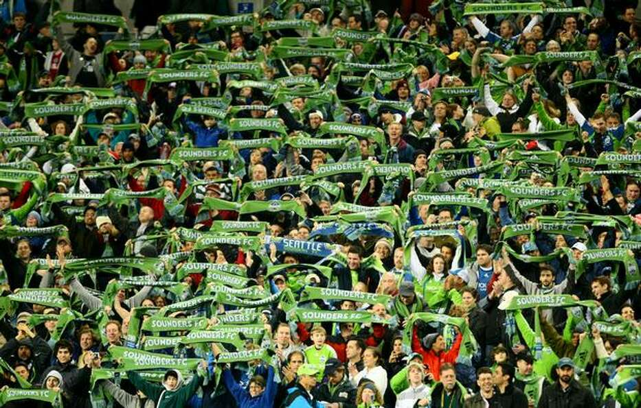 Seattle Sounders FC fans raise their scarves during the season opener on March 19, 2009, at Qwest Fi