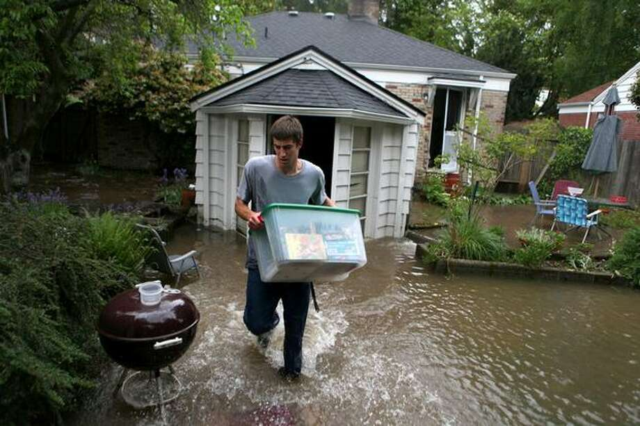 Patrick Ehlers, 18, removes boxes from his flooding home on 24th Avenue Northeast after a water main burst in Seattle's Ravenna neighborhood. The 12-inch water main burst on May 19, 2009. Photo: Joshua Trujillo, Seattlepi.com