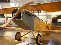 The Curtiss JN-4D Jenny was the first mass-produced American aircraft and used as a WWI trainer, with an instructor yelling to the student from the back seat using a tube into his helmet. This Jenny was made in May 1918 for military service and sold back to Curtiss on May 6, 1919 for reconditioning and civilian resale.