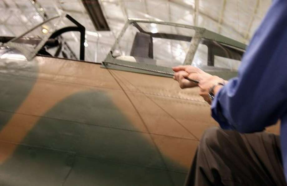 Cory Graff, aviation curator and historian at the Flying Heritage Collection, demonstrates the rope pilots used to get up to the cockpit of the Nakajima Ki-43 Hayabusa. Photo: Aubrey Cohen, Seattlepi.com