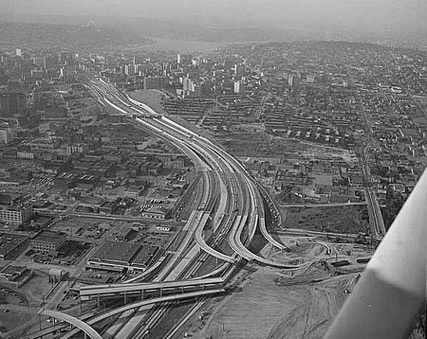 Aerial of freeway construction, Seattle, 1967. Construction of the Tacoma-Seattle-Everett freeway, which opened to traffic in December 1962, took up 6,600 parcels of land, 4,500 of them in Seattle. In 1958-59, the Washington State Highway Department paid homeowners fair market value for their homes, then auctioned the buildings for either removal or salvage. (Seattlepi.com file/MOHAI)