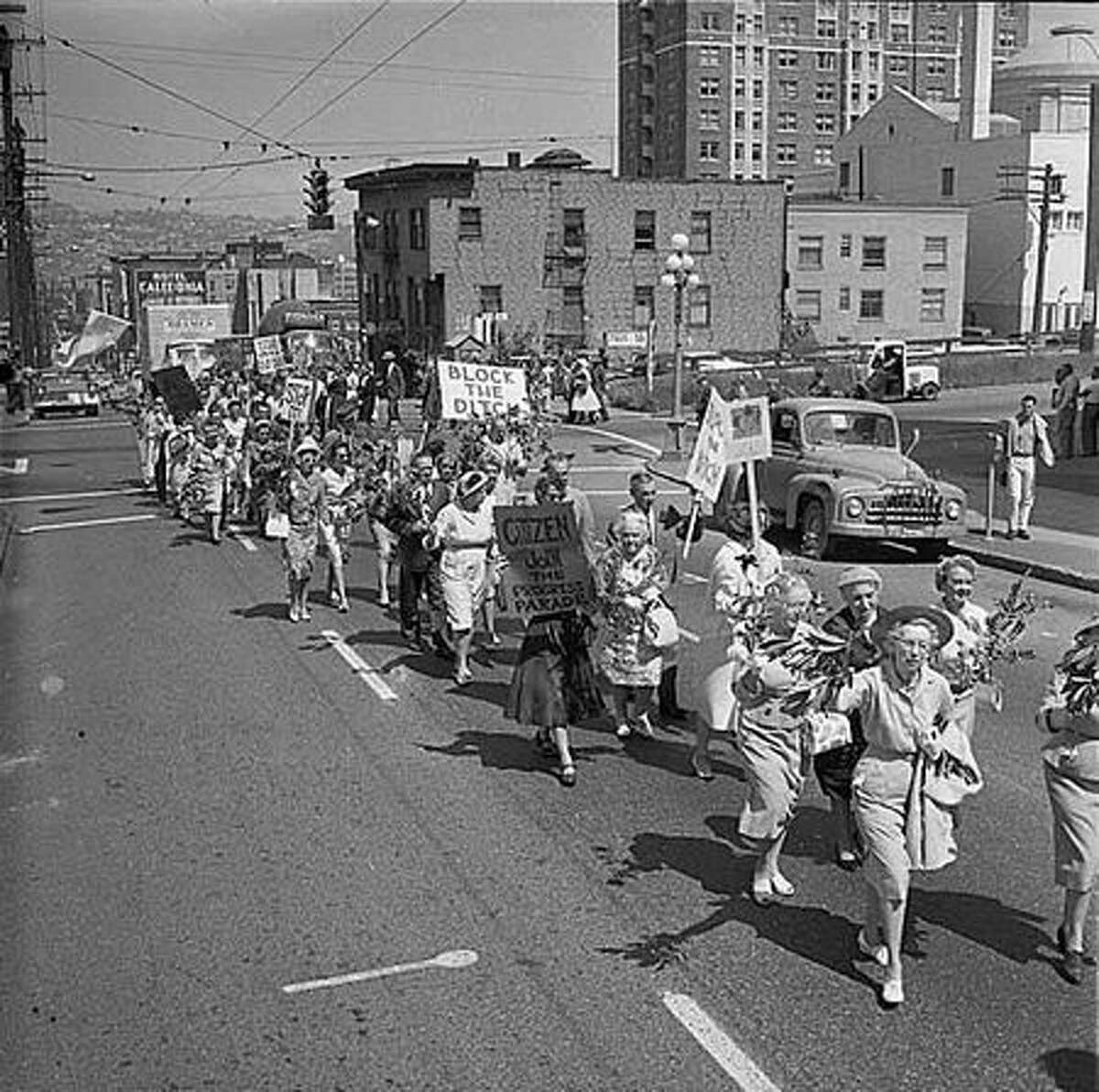 Protesters march across Spring Street demonstrating opposition to freeway construction, Seattle, June 1961. Construction of the Tacoma-Seattle-Everett freeway, which opened to traffic in December 1962, took up 6,600 parcels of land, 4,500 of them in Seattle. In 1958-59, the Washington State Highway Department paid homeowners fair market value for their homes, then auctioned the buildings for either removal or salvage. (Seattlepi.com file/MOHAI)