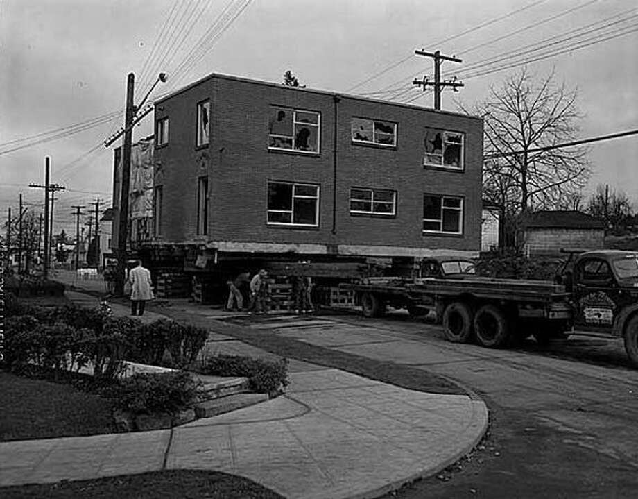 Apartment house at N.E. 68th Street and Weedin Place being moved prior to freeway construction, Seattle, 1960. Construction of the Tacoma-Seattle-Everett freeway, which opened to traffic in December 1962, took up 6,600 parcels of land, 4,500 of them in Seattle. In 1958-59, the Washington State Highway Department paid homeowners fair market value for their homes, then auctioned the buildings for either removal or salvage. (Seattlepi.com file/MOHAI)