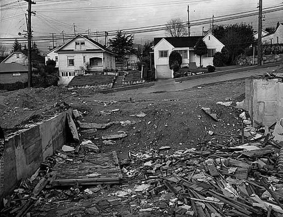 Clearing land for freeway construction, Seattle, 1960. Construction of the Tacoma-Seattle-Everett freeway, which opened to traffic in December 1962, took up 6,600 parcels of land, 4,500 of them in Seattle. In 1958-59, the Washington State Highway Department paid homeowners fair market value for their homes, then auctioned the buildings for either removal or salvage. (Seattlepi.com file/MOHAI)