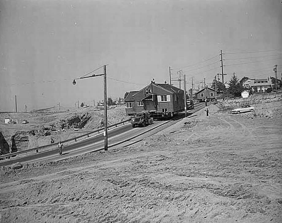 House being moved prior to freeway construction, Seattle, 1963. Construction of the Tacoma-Seattle-Everett freeway, which opened to traffic in December 1962, took up 6,600 parcels of land, 4,500 of them in Seattle. In 1958-59, the Washington State Highway Department paid homeowners fair market value for their homes, then auctioned the buildings for either removal or salvage. (Seattlepi.com file/MOHAI)