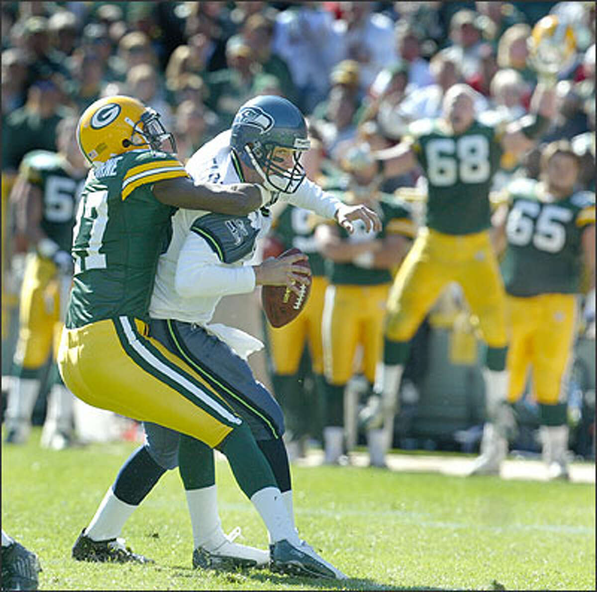 Seahawks quarterback Matt Hasselbeck is sacked near the end of the second quarter for a seven-yard loss by Packers cornerback Michael Hawthorne at the Packer 39-yard-line.