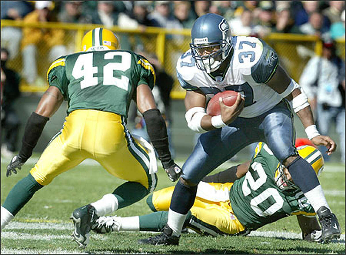 Seahawks running back Shawn Alexander tries to avoid Packer's Darren Sharper after having just run past Marques Anderson in the third quarter.