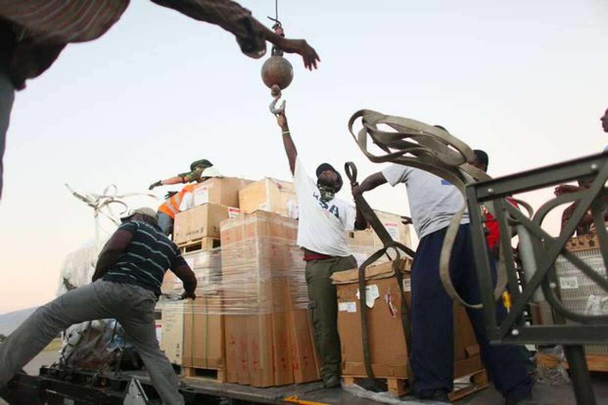 Workers unload communication equpment to rebuild the cellular network in Haiti at Port-au-Prince's International Toussaint Louverture Airport on Sunday. A massive international response has been organized after the devastating 7.0 earthquake, which destroyed much of the capital city.