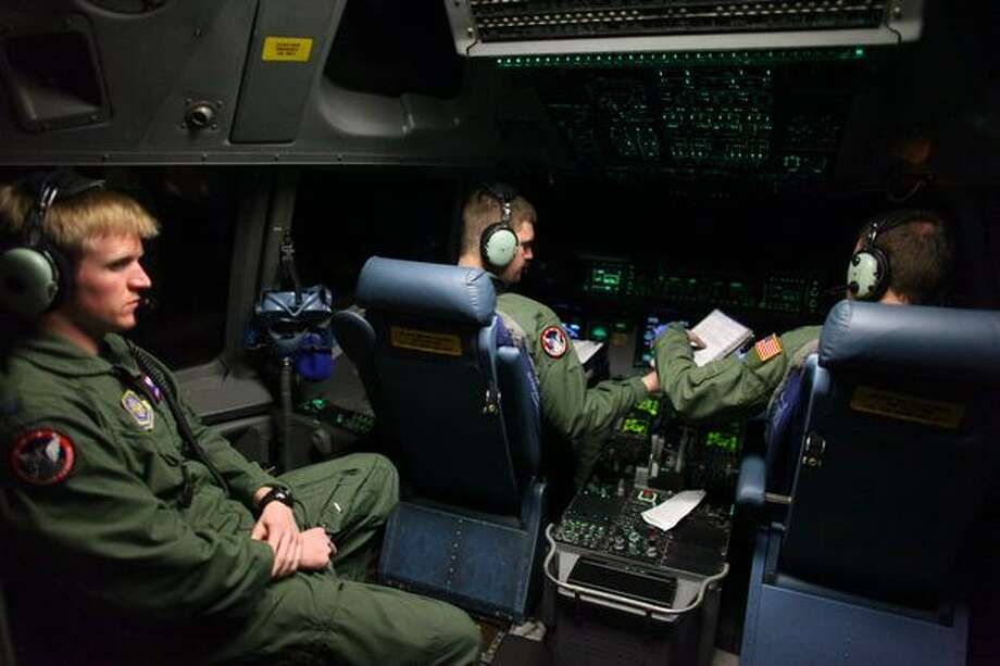 From left, U.S. Air Force 1st Lt. Joe Hurley, 1st Lt. Nate Moseley and Capt. Tony Cappel pilot a C-17 Globemaster to a staging area on the Eastern seaboard from McChord Air Force Base on Sunday. The plane was participating in a massive airlift of personnel and relief supplies into earthquake-damaged Haiti. Photo: Joshua Trujillo, Seattlepi.com