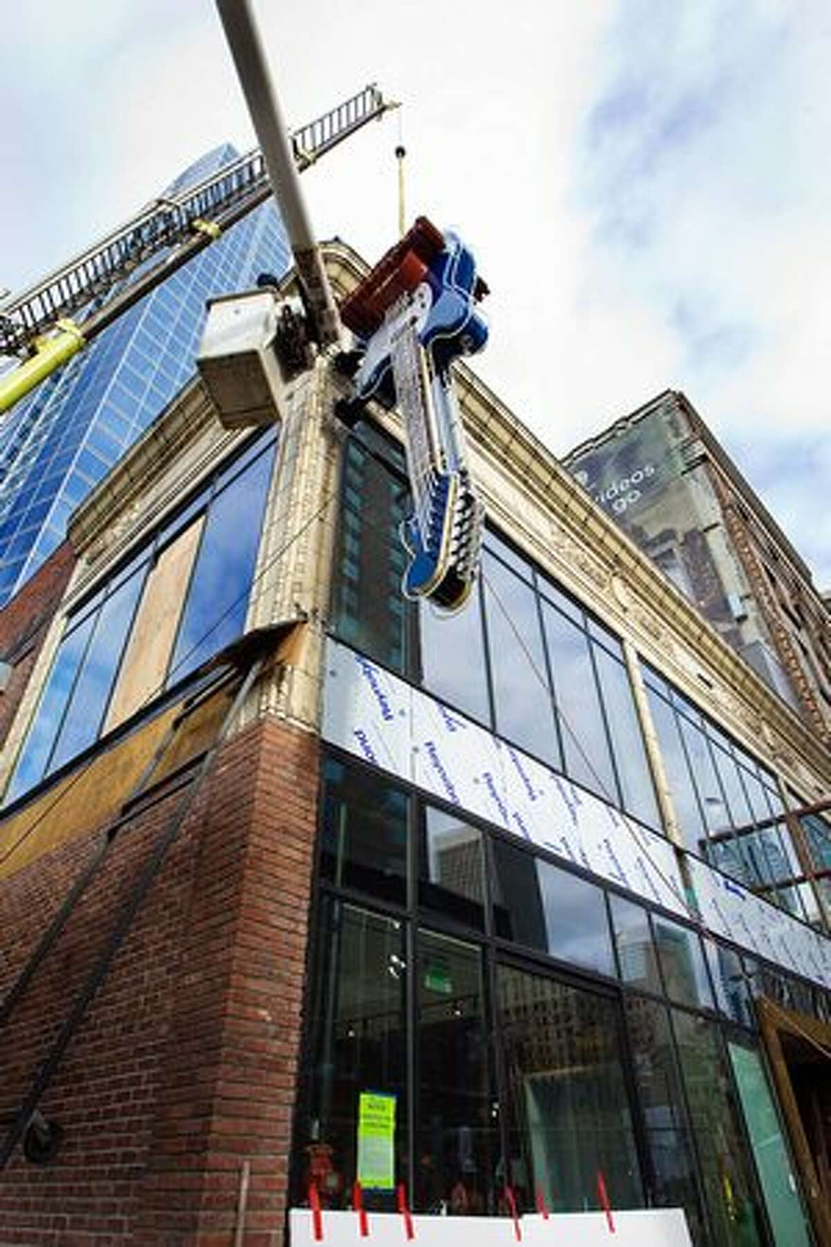 Crews install a model Fender Mustang guitar at 116 Pike St., the site of Seattle's new Hard Rock Cafe. (Photo by Mat Hayward for Hard Rock Cafe Seattle)