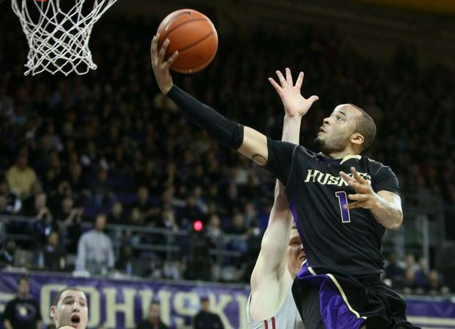 University of Washington Husky Venoy Overton goes up against Washington State University Cougar Charlie Enquist in the first half. Photo: Joshua Trujillo, Seattlepi.com