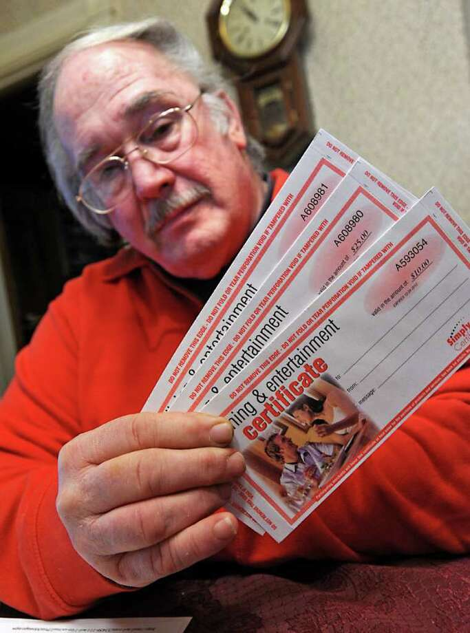 Dennis Mohan holds his expired gift certificates at his home in Troy, NY on Friday, March 25, 2011. (Lori Van Buren / Times Union) Photo: Lori Van Buren