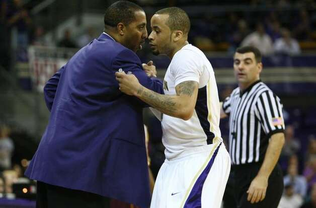 UW's Venoy Overton is greeted by coach Lorenzo Romar as he leaves the court after fouling out. Photo: Joshua Trujillo, Seattlepi.com