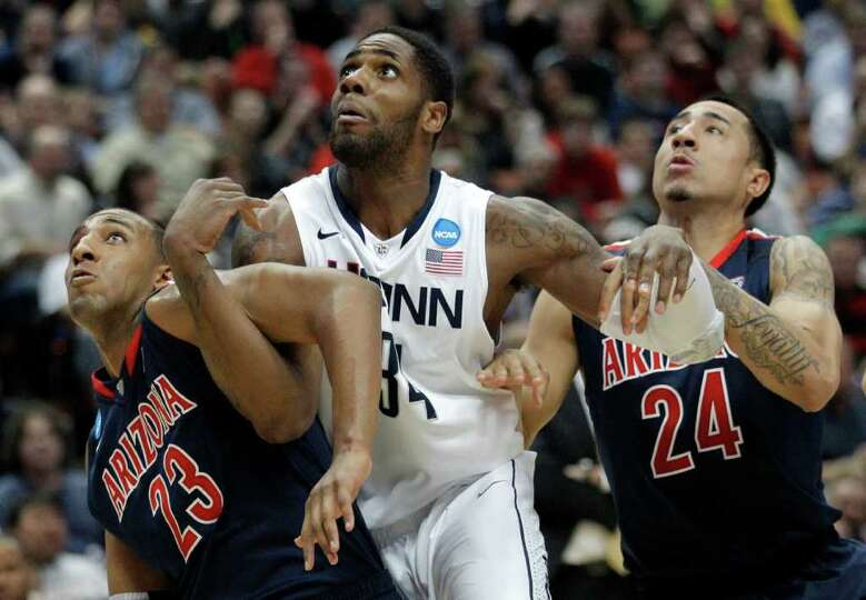Arizona's Derrick Williams, left, with his teammate Brendon Lavender, right,  fights Connecticut's A