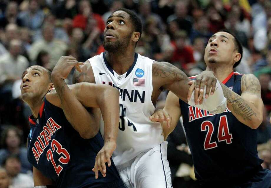Arizona's Derrick Williams, left, with his teammate Brendon Lavender, right,  fights Connecticut's Alex Oriakhi for a rebound during the second half ofthe NCAA West regional college basketball championship game, Saturday, March 26, 2011, in Anaheim, Calif.  (AP Photo/Jae C. Hong) Photo: AP