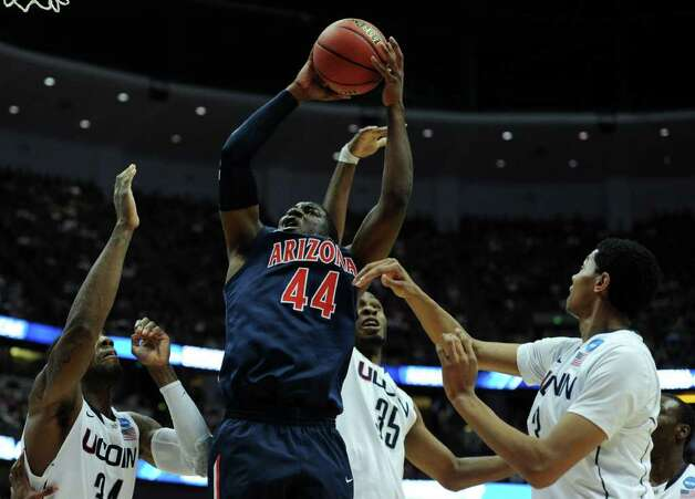 ANAHEIM, CA - MARCH 26:  Solomon Hill #44 of the Arizona Wildcats goes to the basket against Alex Oriakhi #34, Charles Okwandu #35 and Jeremy Lamb #3 of the Connecticut Huskies during the west regional final of the 2011 NCAA men's basketball tournament at the Honda Center on March 26, 2011 in Anaheim, California.  (Photo by Harry How/Getty Images) *** Local Caption *** Solomon Hill;Alex Oriakhi;Charles Okwandu;Jeremy Lamb Photo: Harry How, Getty Images / 2011 Getty Images