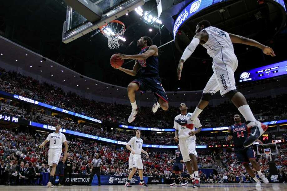 ANAHEIM, CA - MARCH 26:  Jesse Perry #33 of the Arizona Wildcats goes to the basket Alex Oriakhi #34 of the Connecticut Huskies during the west regional final of the 2011 NCAA men's basketball tournament at the Honda Center on March 26, 2011 in Anaheim, California.  (Photo by Harry How/Getty Images) *** Local Caption *** Jesse Perry;Alex Oriakhi Photo: Harry How, Getty Images / 2011 Getty Images