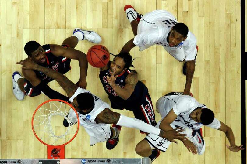 ANAHEIM, CA - MARCH 26:  Jesse Perry #33 of the Arizona Wildcats goes to the basket against Alex Ori