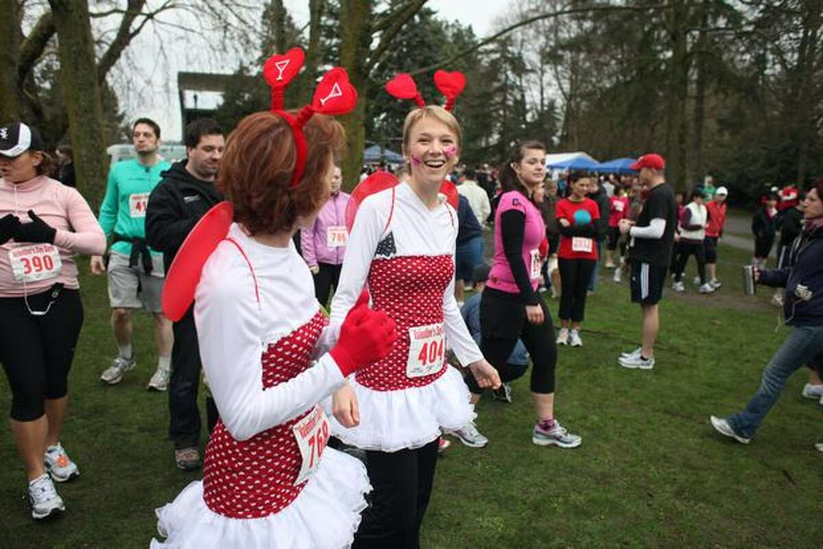 Holly Martin and Mo Gillis make their way to the starting line of the Love 'Em or Leave 'Em Valentine's Day Dash in Green Lake on Saturday morning. The 5K run and walk drew approximately 3,000 participants, according to organizers. (David Ryder/seattlepi.com)