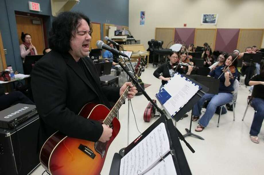 Musician Jon Auer of the Posies sings and plays his guitar during a practice session with the Seattle Rock Orchestra on Wednesday at Shorecrest High School in Shoreline. Photo: Joshua Trujillo, Seattlepi.com