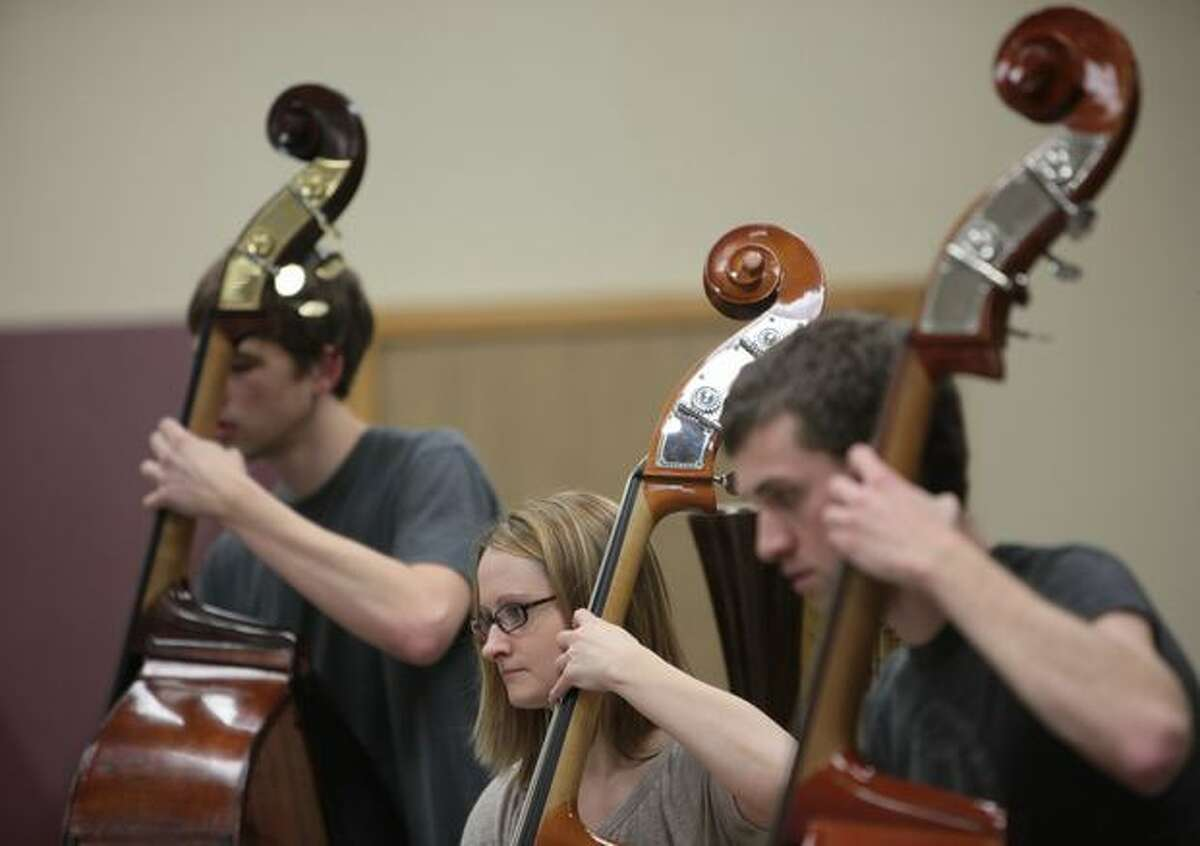 Bassists, from left, Scott Magill, Leslie Woodworth and John Teske play their instruments during a practice session with the Seattle Rock Orchestra.