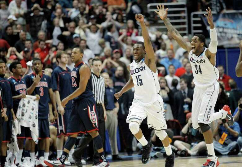 Connecticut's Kemba Walker, center and teammate Alex Oriakhi, right react after Connecticut beats Ar