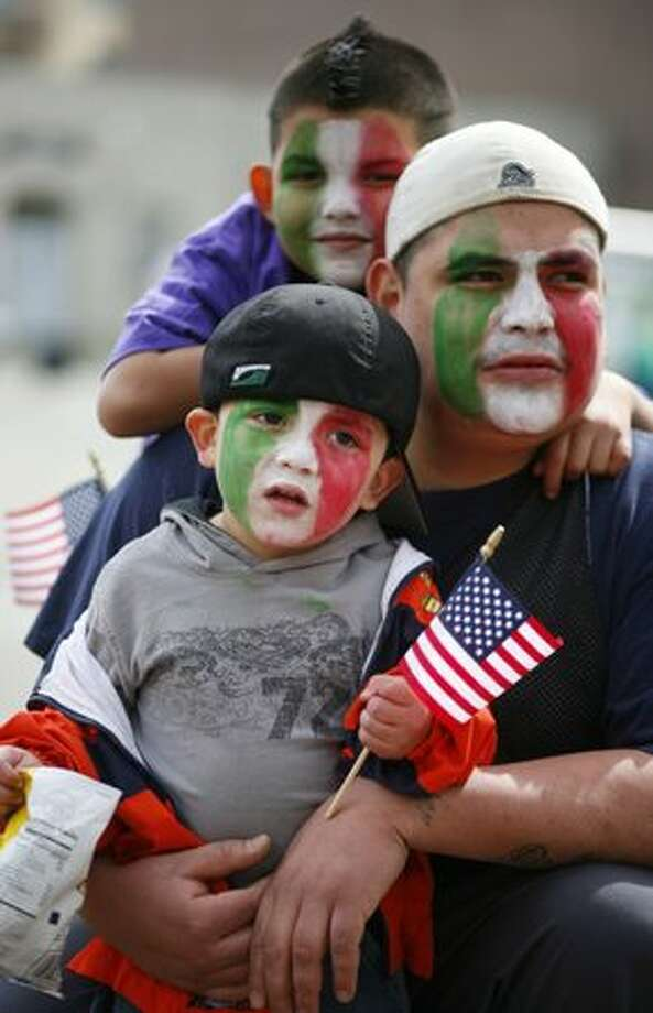 Alex Ledezma of Juarez, Mexico sits with his sons Brandon, 3, and Dylan, 6, during an immigration reform rally in Seattle's Occidental Park on Saturday April 10, 2010. Speaker Pramila Jayapal, executive director of OneAmerica, said her organization is demanding that a bill be introduced in congress for immigration reform by May 1st. Photo: Joshua Trujillo, Seattlepi.com