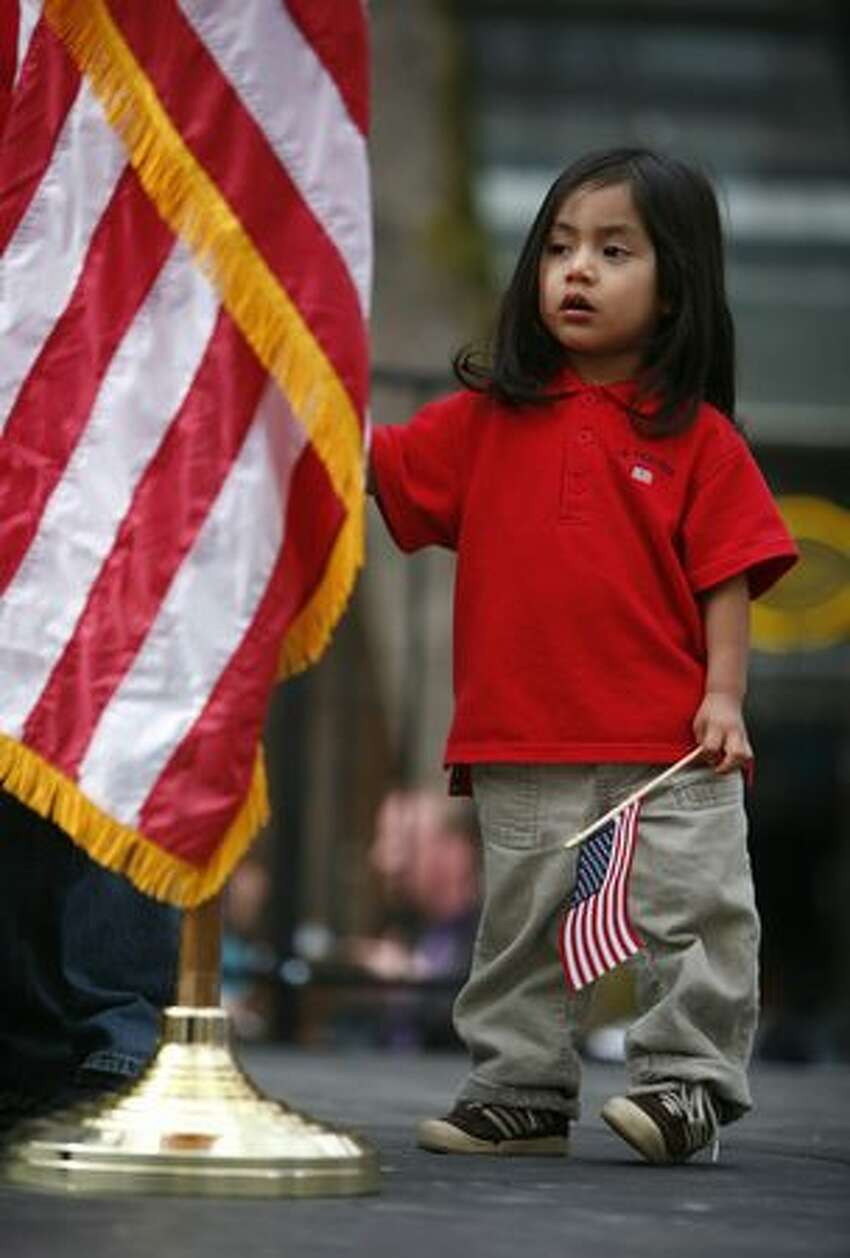 Ivan Hernandez, 2, stands near the podium as his brother Irais, 11, speaks during an immigration reform rally in Seattle's Occidental Park on Saturday April 10, 2010. The boys' dad was detained by immigration officials and may be sent back to his native Mexico. Speaker Pramila Jayapal, executive director of OneAmerica, said her organization is demanding that a bill be introduced in congress for immigration reform by May 1st.