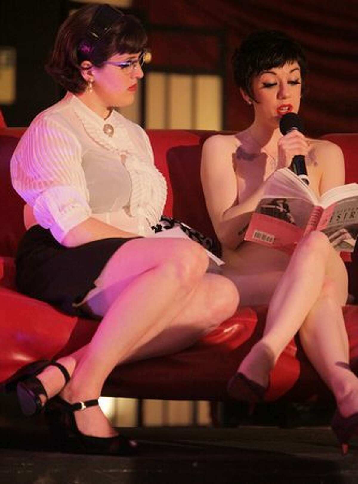 Elsa Von Schmaltz, left, and Polly Wood of Naked Girls Reading share some literature with an audience during the Erotic Art Festival on Friday April 30, 2010 at the Seattle Center Exhibition Hall.